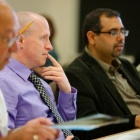 Faculty members engaged in conversation in a school-wide meeting.