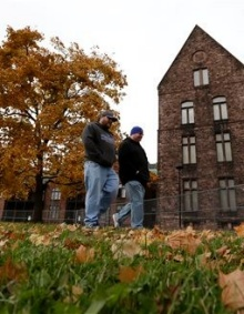 Men walk near the Richardson-Olmstead Complex, a historic site that was once an insane asylum and is being converted to hotel and convention space, Saturday, Nov. 8, 2014, in Buffalo, N.Y. New York state's upstate-downstate divide is alive and well, as Tuesday's election results showed. Cuomo has tried to appeal to upstate with talk of yogurt plants, tourism and economic development initiatives in Buffalo, but the numbers show there's still significant differences when it comes to how the two areas view state government. (AP Photo/Julio Cortez).