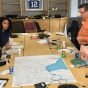A group of urban planning faculty and students and community members from Buffalo stand over a map discussing climate resilience strategies.