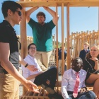 students sitting on their design build project, a wooden structure.