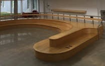 Large curving wooden bench.
