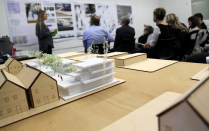 3.5 studio presenting their projects in front of a jury and a site model in the foreground.
