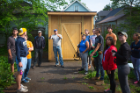 Peter Russell (center rear in blue cap) and Ed Steinfeld (to Russell's right) lead UB students on a tour of a Habitat for Humanity house designed by UB architecture and planning students. Photo: Douglas Levere