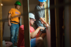 Students attach some drywall underneath a window. Photo: Douglas Levere