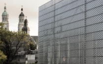 A metal clad box juxtaposes a church in the East Side of Buffalo