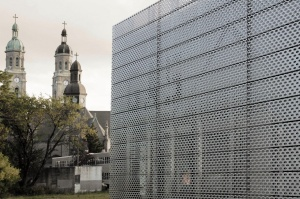A metal clad box juxtaposes a church in the East Side of Buffalo.