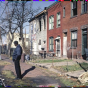 man standing on sidewalk in front of a row of abandoned buildings with debris and trash on the front lawns.