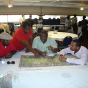 A group of community members working over a map on a table.
