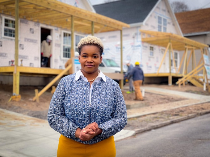 India Walton standing in front of a house being constructed at the fruit belt district.