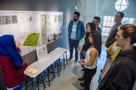 The NOMAS team regroups after their win. The [WEAVING IN] Sunnyside project model is visible below the team's presentation board; the students integrated the natural environment into their design in order to best utilize the expansive site. The main building, the proposed school, is highlighted on the left side of the model.