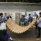 Miguel Guitart and students hold up wooden structure during final review.