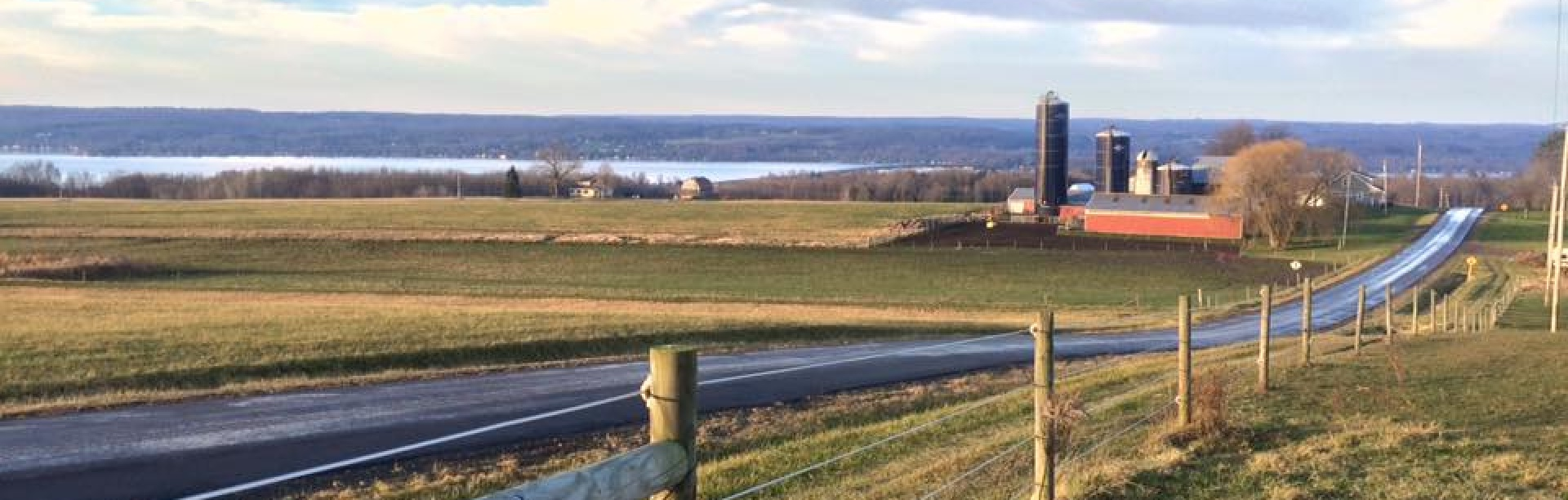 Farm land and barns in the horizon along a country road in Chautauqua county, New York.