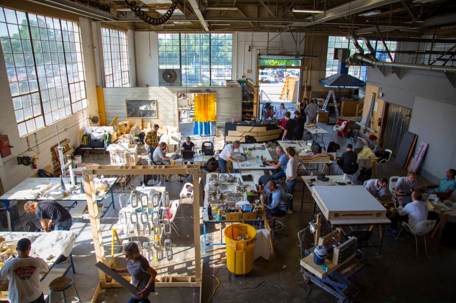 Workshop crowded with teams working on ceramics at many workstations.