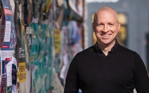 Dan Hess stands in an urban environment with wall covered in posters