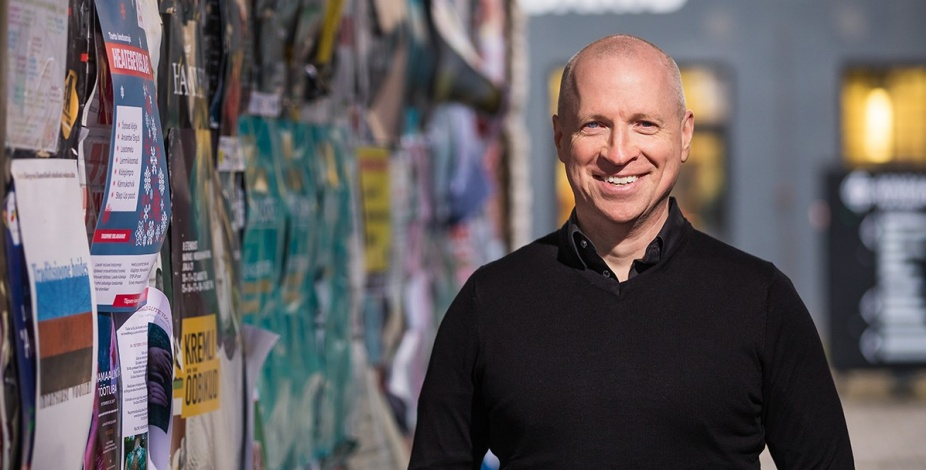 Dan Hess stands in an urban environment with wall covered in posters.