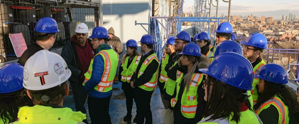 Group of Students wearing protective helmets on construction site.