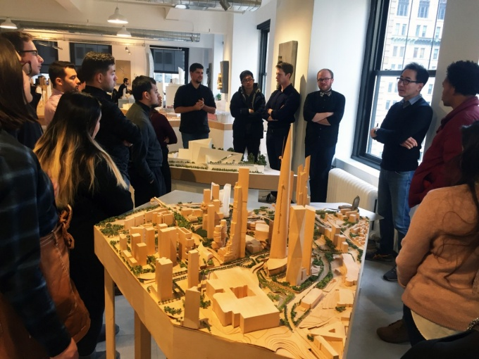 Group of student surround large site model in office.