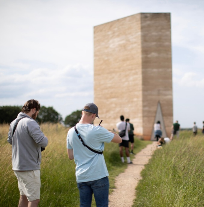 Students stand in a field, sketching a tall, modern building.