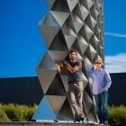 Nicholas Bruscia and Christopher Romano stand in front of curving metal wall.