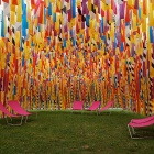 An outdoor space is created by a metal frame from which thousands of vibrant ribbons are hung with lounge lawn chairs positioned beneith.