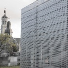 Perforated Metal facade juxtaposed with traditional church towers in the background.