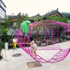 Children playing on curved grid structure.