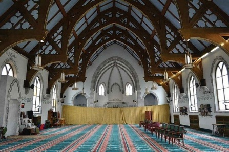 Interior view of the Jami Masjid show the replaced windows and Turkish carpeting for Islamic prayer. The murals have been painted sky blue and the walls are adorned with Arabic calligraphy.