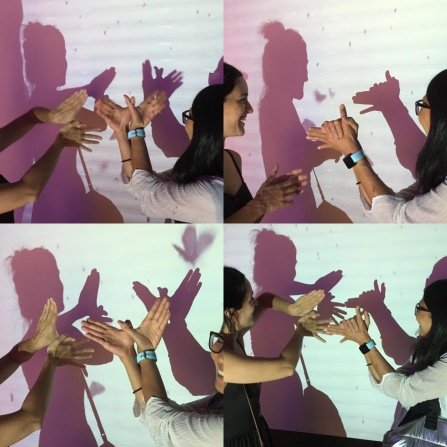 Joyce Hwang and student make shadow puppets in front of a projector.