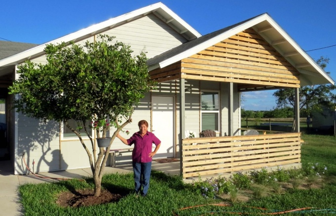 A resident stands in front of her MiCasita home which features a front porch and lush landscaping.