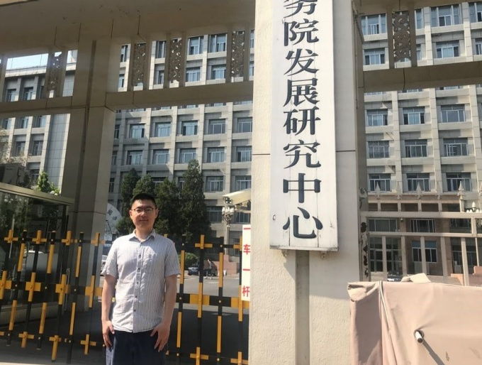 Xuan Sun standing in front of his office.