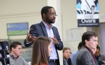 Professor Boamah pictured speaking with students in foreground.