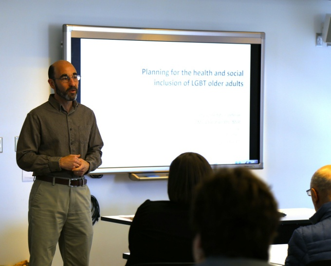 "Professor Robert Silverman Standing in front of large presentation monitor reading ""Planning for the health and social inclusion of LGBT older adults""."