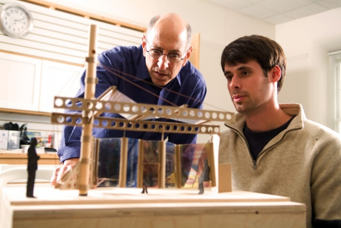 Ed Steinfeld examining a wood model with a student.